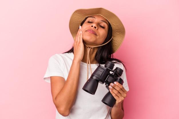 Giovane donna latina che tiene in mano un binocolo isolato su sfondo rosa scioccata, ha ricordato un incontro importante.