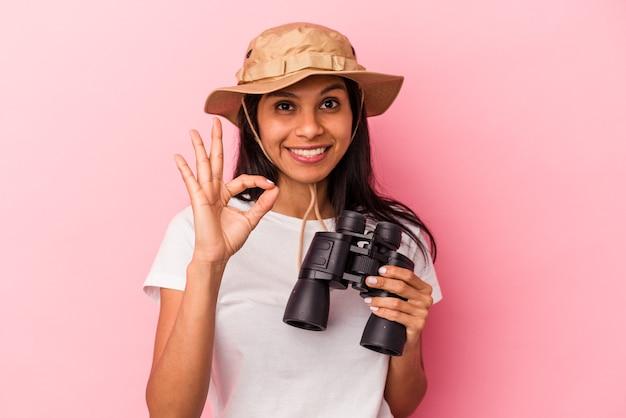 Giovane donna latina che tiene il binocolo isolato su sfondo rosa allegro e fiducioso che mostra gesto ok.