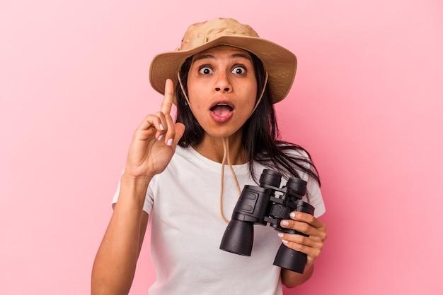 Giovane donna latina che tiene il binocolo isolato su sfondo rosa avente un'idea, concetto di ispirazione.