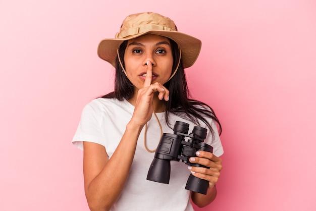 Giovane donna latina che tiene in mano un binocolo isolato su sfondo rosa mantenendo un segreto o chiedendo silenzio.