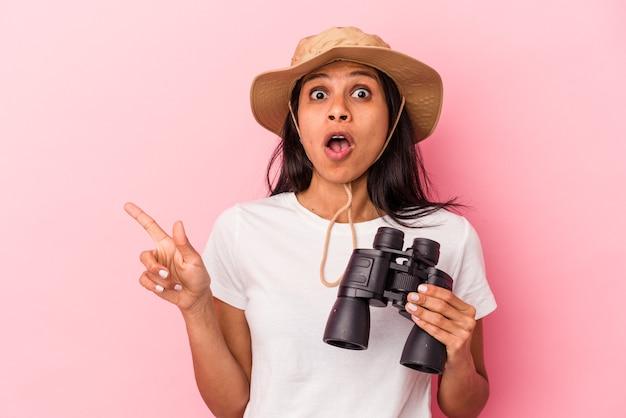 Giovane donna latina che tiene il binocolo isolato su sfondo rosa che punta al lato