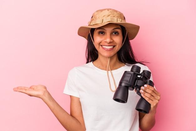 Giovane donna latina che tiene il binocolo isolato su sfondo rosa che mostra uno spazio di copia su un palmo e tiene un'altra mano sulla vita.