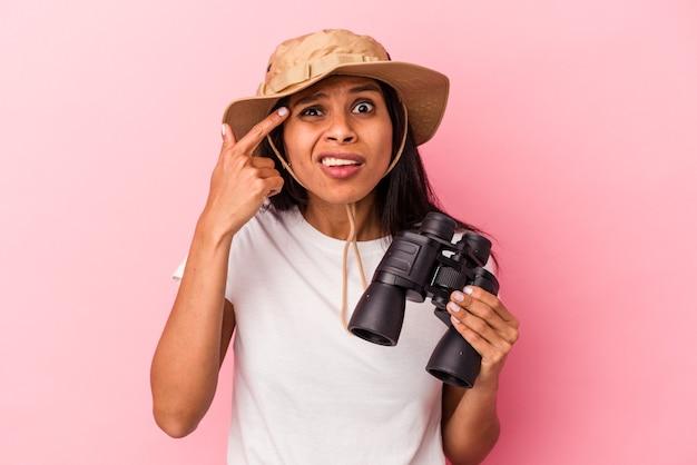 Giovane donna latina che tiene il binocolo isolato su sfondo rosa che mostra un gesto di delusione con l'indice.