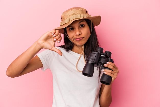 Giovane donna latina che tiene il binocolo isolato su sfondo rosa che mostra un gesto di antipatia, pollice in giù. concetto di disaccordo.