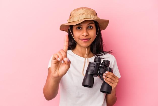 Giovane donna latina che tiene il binocolo isolato su sfondo rosa che mostra il numero uno con il dito.