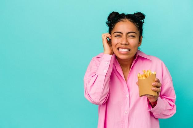 Giovane donna latina che tiene i chip isolati su sfondo blu che copre le orecchie con le mani.