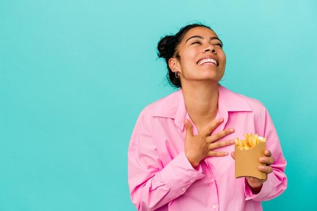 La giovane donna latina che tiene i chip isolati su sfondo blu ride ad alta voce tenendo la mano sul petto.