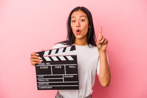 Giovane donna latina che tiene il ciak isolato su sfondo rosa con qualche grande idea, concetto di creatività.