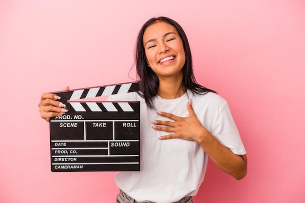 La giovane donna latina che tiene il ciak isolato su sfondo rosa ride ad alta voce tenendo la mano sul petto.