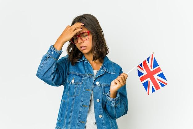 Giovane donna latina che tiene una bandiera inglese isolata su priorità bassa bianca che ha un mal di testa, toccando la parte anteriore del viso.