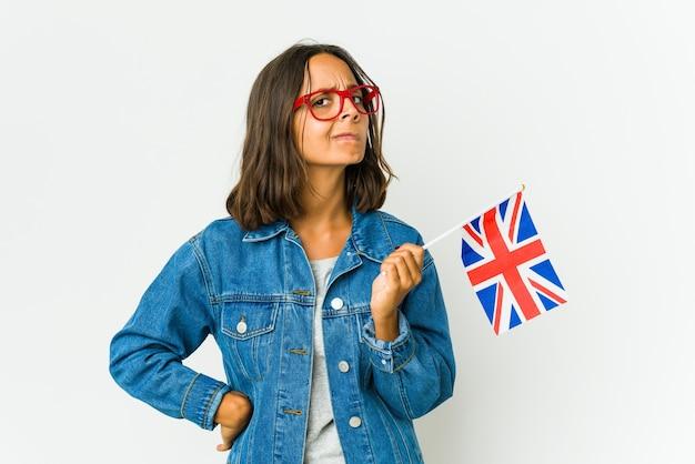 La giovane donna latina che tiene una bandiera inglese isolata su bianco confusa, si sente dubbiosa e insicura.
