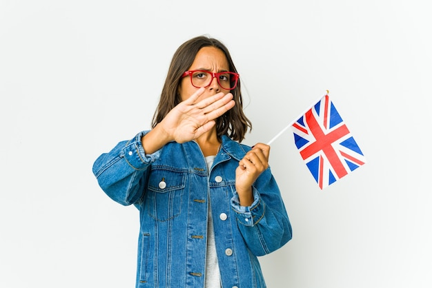Giovane donna latina che tiene una bandiera inglese isolata su bianco facendo un gesto di diniego