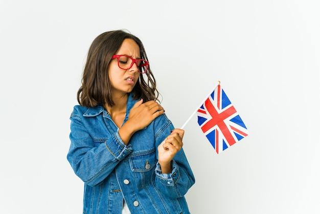 Giovane donna latina che tiene una bandiera inglese isolata su bianco che ha un dolore alla spalla.