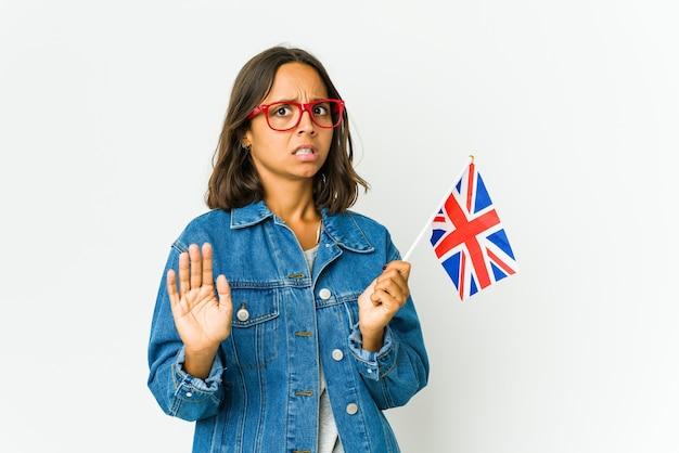 Giovane donna latina che tiene una bandiera inglese isolata su bianco che rifiuta qualcuno che mostra un gesto di disgusto.