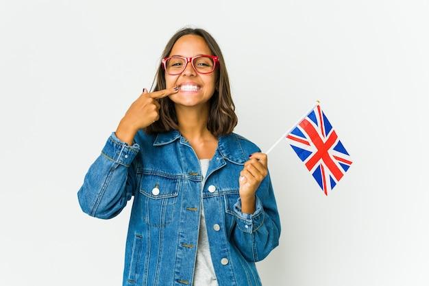 Giovane donna latina che tiene una bandiera inglese isolata sui sorrisi bianchi, puntando le dita alla bocca.