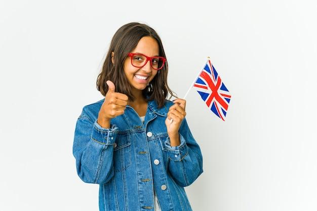 Giovane donna latina che tiene una bandiera inglese isolata su bianco che sorride e che alza il pollice in su
