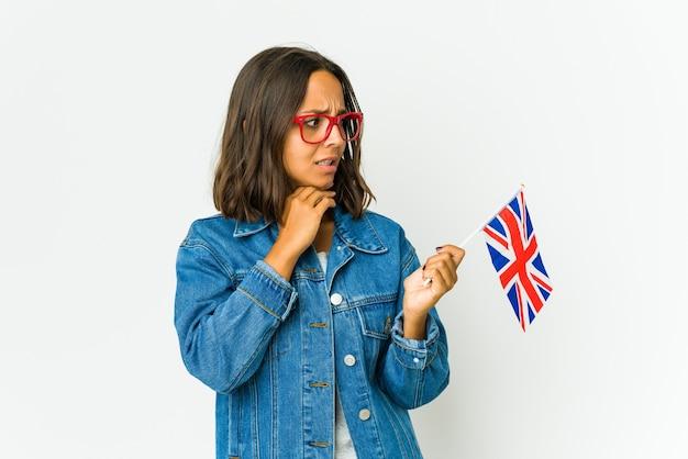 Giovane donna latina che tiene una bandiera inglese isolata su bianco che tocca la parte posteriore della testa, pensando e facendo una scelta.