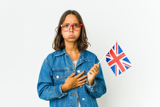 La giovane donna latina che tiene una bandiera inglese isolata sul muro bianco soffia sulle guance, ha un'espressione stanca. concetto di espressione facciale.