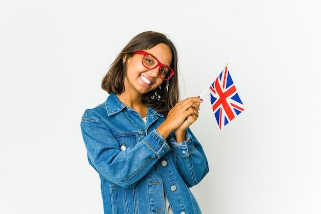 Giovane donna latina che tiene una bandiera inglese isolata sulla parete bianca che si sente energica e comoda, strofinando le mani fiducioso.