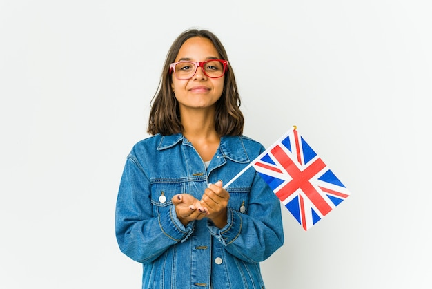 Giovane donna latina che tiene una bandiera inglese isolata sulla parete bianca che tiene qualcosa con le palme, offrendo alla macchina fotografica.