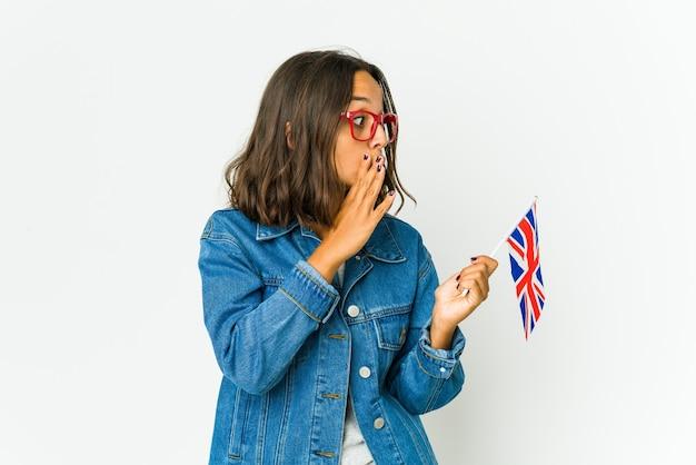 La giovane donna latina che tiene una bandiera inglese isolata sulla parete bianca sta dicendo una notizia di frenata calda segreta e sta guardando da parte