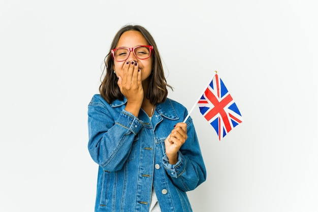 Giovane donna latina che tiene una bandiera inglese isolata sul muro bianco che ride di qualcosa, che copre la bocca con le mani.