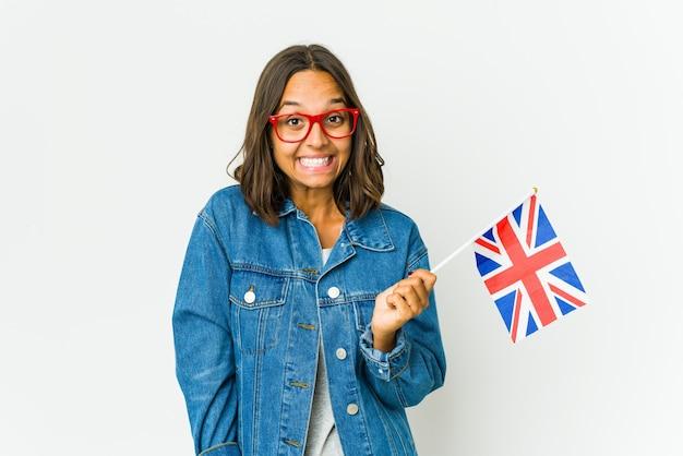 La giovane donna latina che tiene una bandiera inglese isolata sul muro bianco ride e chiude gli occhi, si sente rilassata e felice.