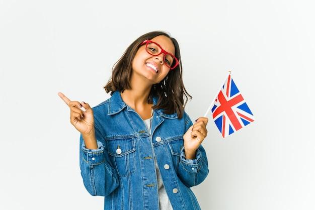 Giovane donna latina che tiene una bandiera inglese isolata sul muro bianco che punta a diversi spazi di copia, scegliendone uno, mostrando con il dito.
