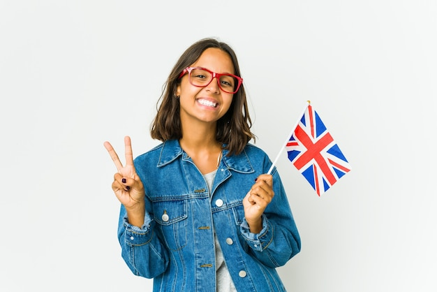 Giovane donna latina che tiene una bandiera inglese isolata sul muro bianco che mostra il numero due con le dita.