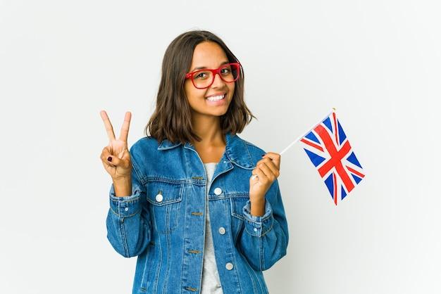 Giovane donna latina che tiene una bandiera inglese isolata sul muro bianco che mostra il segno di vittoria e che sorride ampiamente.