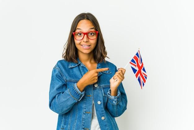 Giovane donna latina che tiene una bandiera inglese isolata sul muro bianco che sorride allegramente indicando con l'indice lontano.
