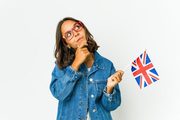Giovane donna latina che tiene una bandiera inglese isolata sul muro bianco pensando e guardando in alto, riflettendo, contemplando, avendo una fantasia.