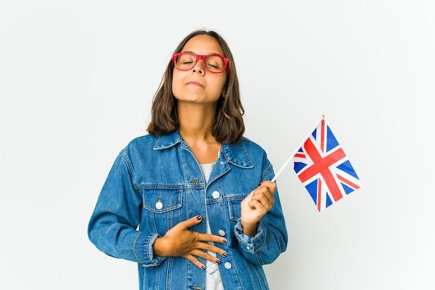 La giovane donna latina che tiene una bandiera inglese isolata sulla parete bianca tocca la pancia, sorride delicatamente, mangia e concetto di soddisfazione.