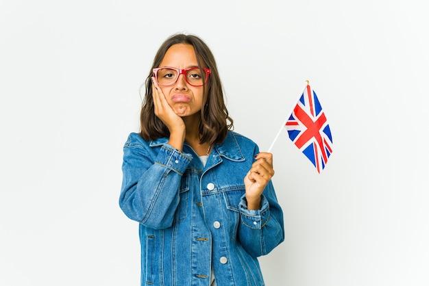 Giovane donna latina che tiene una bandiera inglese isolata sul muro bianco che è annoiata, affaticata e ha bisogno di una giornata di relax.