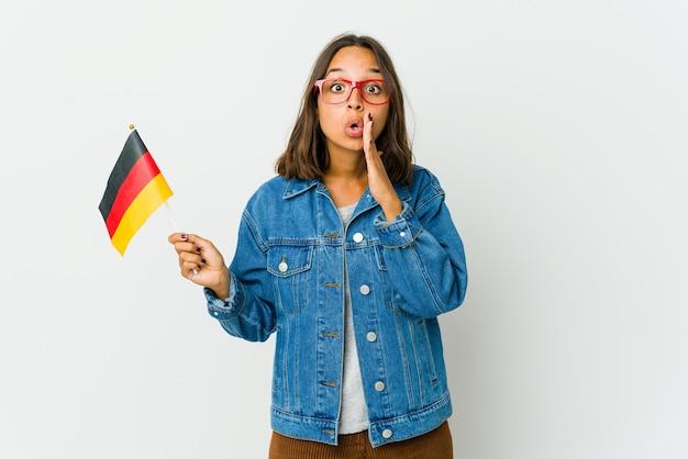 La giovane donna latina che tiene una bandiera tedesca isolata su fondo bianco sta dicendo una notizia di frenata calda segreta e sta guardando da parte