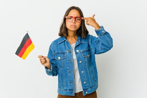 La giovane donna latina che tiene una bandiera tedesca isolata su bianco si è concentrata su un compito, mantenendo gli indici che puntano la testa.
