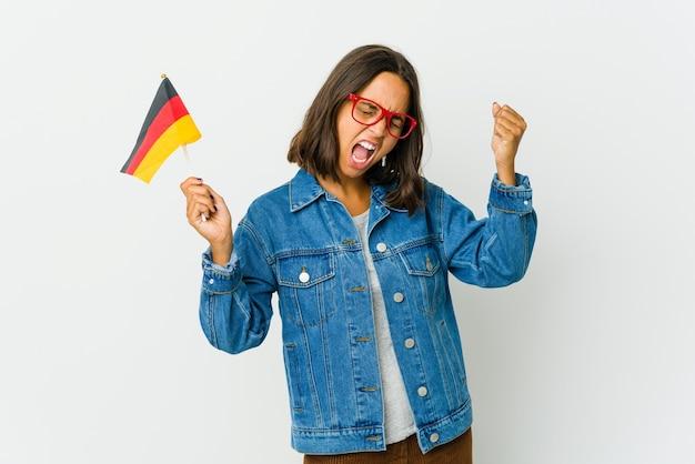 Giovane donna latina che tiene una bandiera tedesca isolata sul pugno di sollevamento bianco dopo una vittoria, concetto del vincitore.