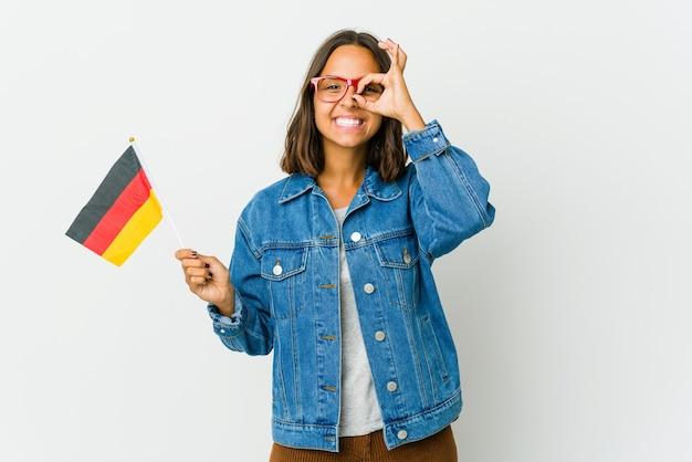 La giovane donna latina che tiene una bandiera tedesca isolata sulla parete bianca ha eccitato mantenendo il gesto giusto sull'occhio.