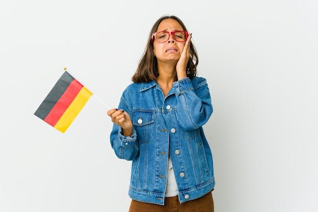 Giovane donna latina che tiene una bandiera tedesca piagnucolando e piangendo sconsolato.