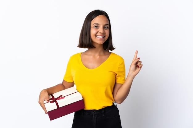 Giovane donna latina che tiene un regalo isolato su bianco che mostra e che alza un dito in segno del meglio