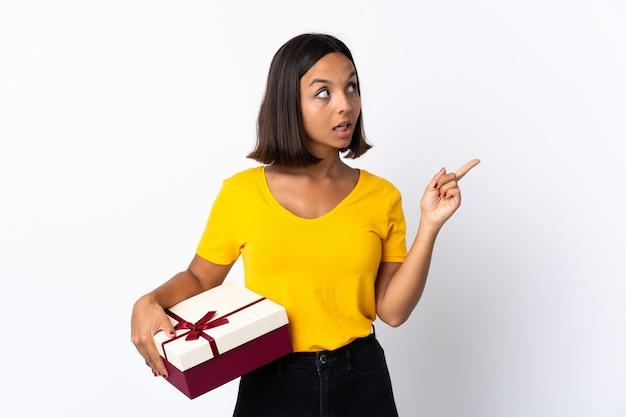Giovane donna latina che tiene un regalo