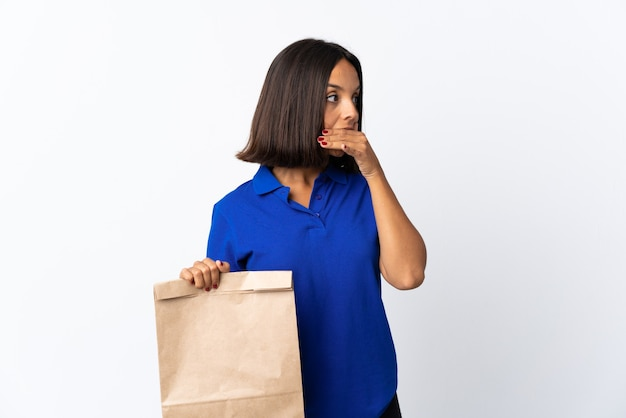 Giovane donna latina in possesso di un sacchetto della spesa isolato su bianco facendo gesto di sorpresa mentre guarda al lato