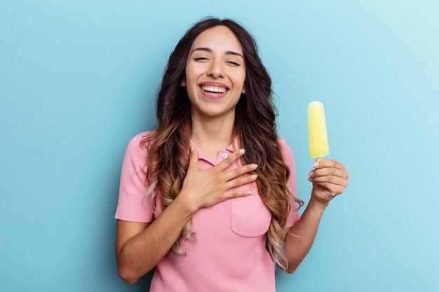 La giovane donna latina che tiene il gelato isolato su sfondo blu ride ad alta voce tenendo la mano sul petto.