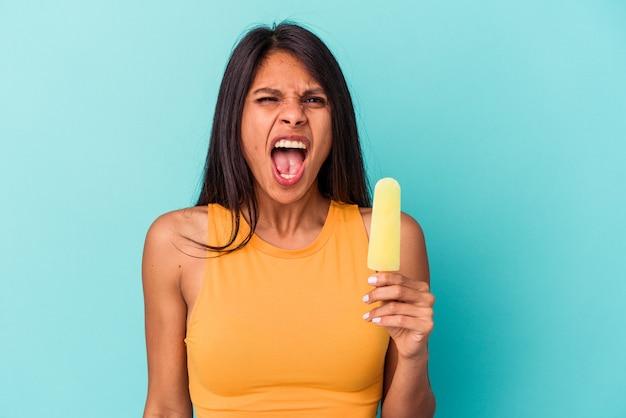 Giovane donna latina che tiene il gelato isolato su sfondo blu urlando molto arrabbiato e aggressivo.
