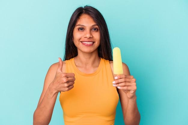 Giovane donna latina che tiene il gelato isolato su sfondo blu sorridente e alzando il pollice thumb