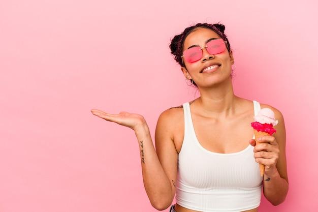 Giovane donna latina che tiene un gelato isolato su sfondo rosa che mostra uno spazio di copia su un palmo e tiene un'altra mano sulla vita.