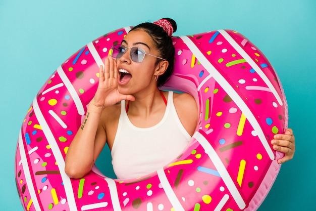 Giovane donna latina che tiene una ciambella gonfiabile isolata su sfondo blu gridando e tenendo il palmo vicino alla bocca aperta.