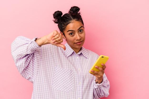 Giovane donna latina in possesso di un telefono cellulare isolato su sfondo rosa che mostra un gesto di antipatia, pollice in giù. concetto di disaccordo.