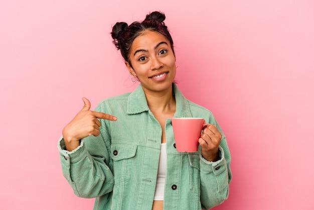Giovane donna latina in possesso di una tazza isolata su sfondo rosa persona che punta a mano a uno spazio copia camicia, orgogliosa e fiduciosa