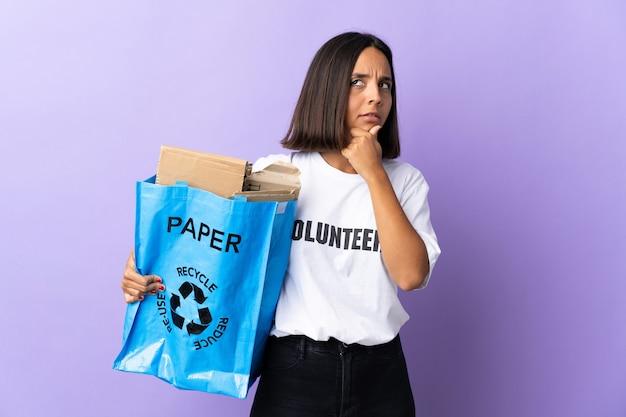 Giovane donna latina che tiene un sacchetto di riciclaggio pieno di carta da riciclare isolato su viola che ha dubbi e con l'espressione del viso confuso